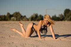 Lovely sexy girl lying on sand in black swimsuit Stock Image