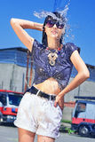 Lovely wet woman, water drops, hands up, short shorts,black long hair and glasses in the background trucks Royalty Free Stock Image