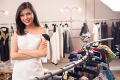 Lovely shop owner. Portrait of a lovely shop owner standing near the rack of clothes hangings on the foreground royalty free stock photo