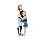 Lovely sibling sisters laughing and hugging. Lovely sibling sisters in jeans and black tanktops laughing and hugging each other Stock Images