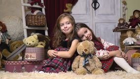 Relaxing girls sit next to each other and smile, toys and gifts are scattered around stock video