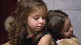 Two little girls sit leaning against each other. Lovely sisters are tired and sitting next to each other stock video