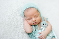 Lovely sleeping baby with blue hat, panties and toy Stock Photos