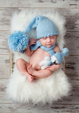 Lovely sleeping baby in hat with big pompon on fluffy cot. Lovely sleeping baby in blue hat with big pompon on fluffy cot, top view Royalty Free Stock Photo