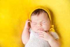 Lovely sleeping newborn baby girl. In white knitted fluffy bodysuite and yellow hat lies on her back on a vivid yellow blanket Stock Photos