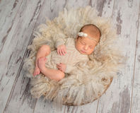 Lovely sleeping newborn baby in knitted jumpsuit in basket Stock Photo