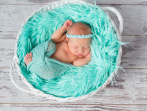 Lovely sleeping newborn girl in round cot with turquoise blanket Stock Images