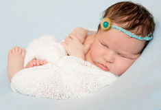 Lovely sleeping wrapped baby with bare feet Stock Photo