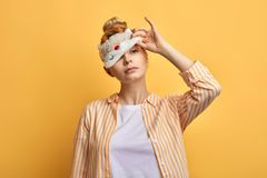 Lovely sleepy lady trying to take off eyemask in the morning royalty free stock image