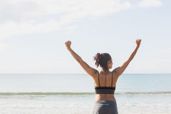 Lovely slender woman stretching her arms on the beach Royalty Free Stock Photos
