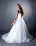 Lovely slim brunette posing in chic wedding dress Royalty Free Stock Images