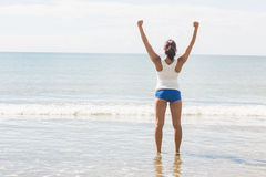 Lovely slim woman standing on beach raising her arms Royalty Free Stock Photography