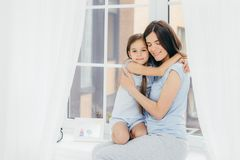 Lovely small child with pleasant appearance embraces her mother, expresses love and good feeling or attitude, sit on window sill,. Enjoy domestic atmosphere and royalty free stock images