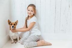 Lovely small female child plays with her dog in white room, sit. On floor, have good relationship, cuddles favourite pet. Little schoolgirl likes animals stock photos