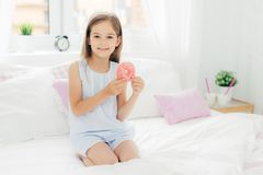 Lovely small girl holds delicious doughnut in hands, going to have breakfast, poses on bed in cozy white bedroom, looks at camera stock images