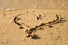 Lovely small heart sketched in salt  sand at beach.  Stock Photos