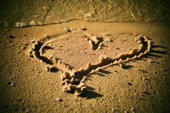 Lovely small heart sketched in salt  sand at beach. Evening warm colors of sunset. Royalty Free Stock Photography