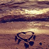 Lovely small heart sketched in salt sand at beach. Evening warm colors of sunset mirror in water level. royalty free stock photography