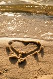 Lovely small heart sketched in salt  sand at beach. Evening warm colors of sunset mirror in water level. Stock Image