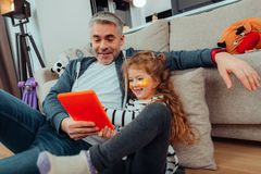 Lovely small long-haired girl and her father in sportswear looking happy stock photo