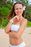 Lovely smiley woman with flower in her hair. Against exotic nature Royalty Free Stock Photo