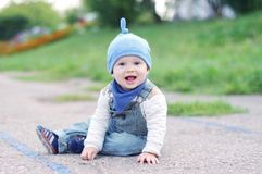 Lovely smiling baby sitting on ground outdoors Royalty Free Stock Image