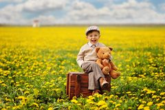 A lovely, smiling boy sitting on the box with teddy bear at the springtime. Hazel tree stock photos