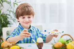 Lovely smiling child painting eggs Stock Images
