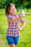 Lovely smiling girl posing and taking selfie with smartphone. In sunny day in summer park. Teenage girl taking picture with smartphone royalty free stock photo
