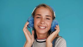 Lovely smiling girl is wearing big blue headphones listening to music inside of a studio. Hands on the headphones. Cute stock video footage