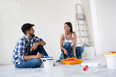 Lovely smiling happy couple painting new home. New house renovation royalty free stock images