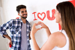 Lovely smiling happy couple painting new home. Hew house renovation stock photo