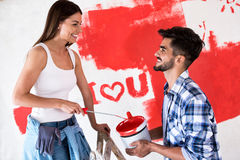Lovely smiling couple painting new home,new house renovation. Lovely smiling happy couple painting new home,new house renovation stock photography