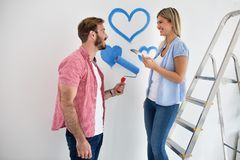 Lovely smiling happy couple painting their new home. Lovely smiling happy couple painting new home royalty free stock photography