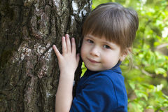 Lovely smiling little girl standing near big tree on green grass Stock Photography