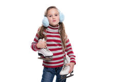 Lovely smiling little girl wearing colorful striped sweater and headdress, holding skates isolated on white background. Winter clothes Royalty Free Stock Photos