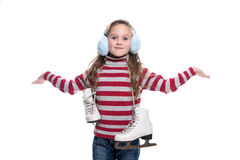 Lovely smiling little girl wearing colorful striped sweater and headdress, holding skates isolated on white background. Winter clothes Royalty Free Stock Images
