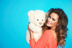 Lovely smiling woman in knitted clothes holding teddy bear Royalty Free Stock Image
