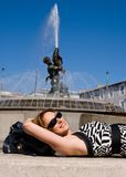 Lovely smiling woman lying by fountain in Rome Stock Image