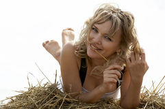 Lovely smiling woman lying on haystack outdoors Stock Photo