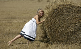 Lovely smiling woman plying with haystack outdoors Royalty Free Stock Photo