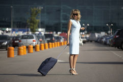 Lovely smiling woman traveling with a suitcase Stock Images