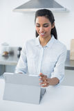 Lovely smiling woman using her tablet standing in bright kitchen Royalty Free Stock Photography