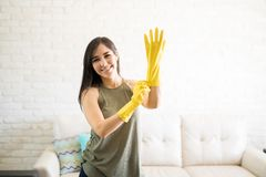 Lovely smiling woman in yellow gloves. Housekeeping lady putting latex gloves on and prepare to clean house Stock Photo