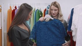 Lovely smiling young woman with friend choosing evening dress in clothing shop stock video