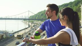 Lovely sports couple relaxing after morning workout in an urban city. Handsome sportsman talking to his girlfriend while resting together after workout. Happy stock video footage