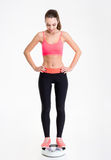 Lovely sportswoman standing on weighing scale and looking down Royalty Free Stock Photo
