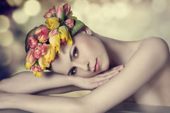 Lovely spring girl. Lovely beauty girl with spring floral wreath, colorful make-up, fresh skin and naked shoulders lying on a table and looking in camera with royalty free stock photo