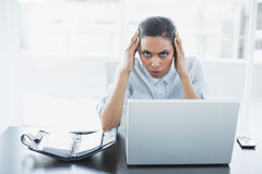 Lovely stern businesswoman suffering from headache Stock Photos