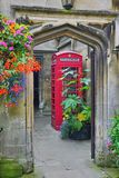 Walkway through arched doorway, flowers, phone booth, inside Magdalen College, Oxford stock images